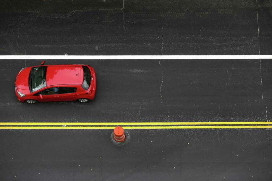 A car drives Wednesday, April 12, 2018 between new paint markings on Main street in downtown San Antonio. Main street and the parallel Soledad street in downtown are both being converted to two-way roads. Photo: William Luther, Staff / San Antonio Express-News / © 2018 San Antonio Express-News