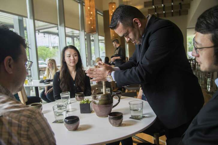 Elvis Espinoza prepares a pitcher of Oaxacan hot chocolate tableside for David Owen, from left, Cici Liu and Xuan Huang, at Xochi in Houston. Tableside service is trending nationwide.