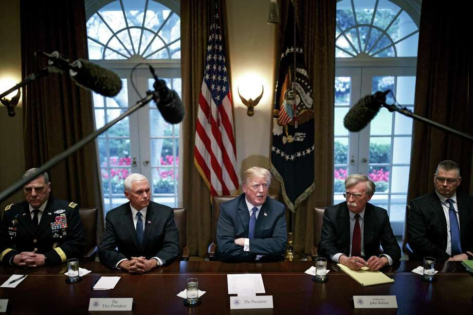 President Donald Trump is flanked by Vice President Mike Pence, left, and National Security Adviser John Bolton as he meets with senior military leaders at the White House in Washington, April 9, days before the president authorized missile strikes against Syria for use of chemical weapons. It's clear that such strikes alone will not help the Syrian people. Photo: TOM BRENNER /NYT / NYTNS