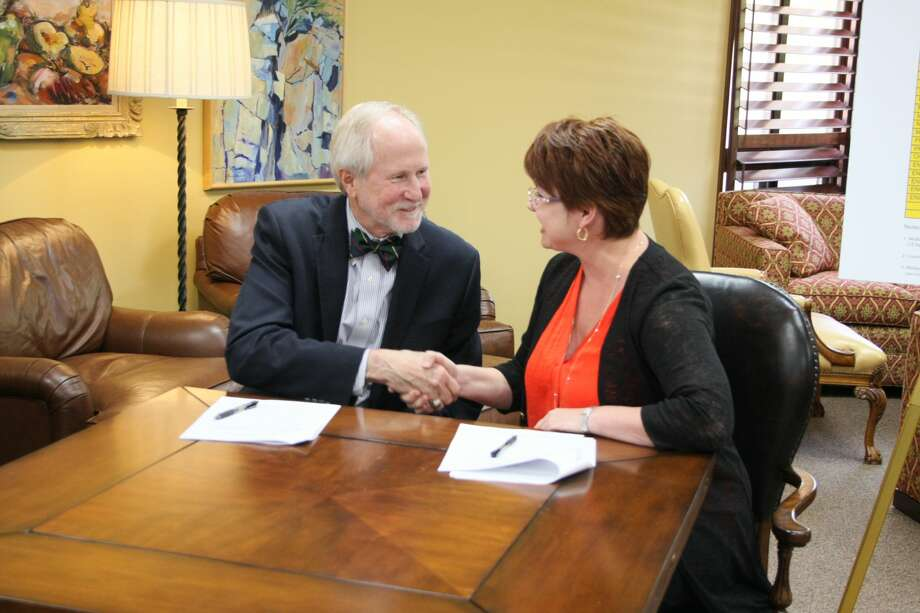 Midland College President Steve Thomas and UTPB President Sandra Woodley shake hands after signing an agreement to collaborate on an academic pathway for engineering students, allowing the transfer of credits between the two schools.  Photo courtesy of Midland College Photo: James Durbin