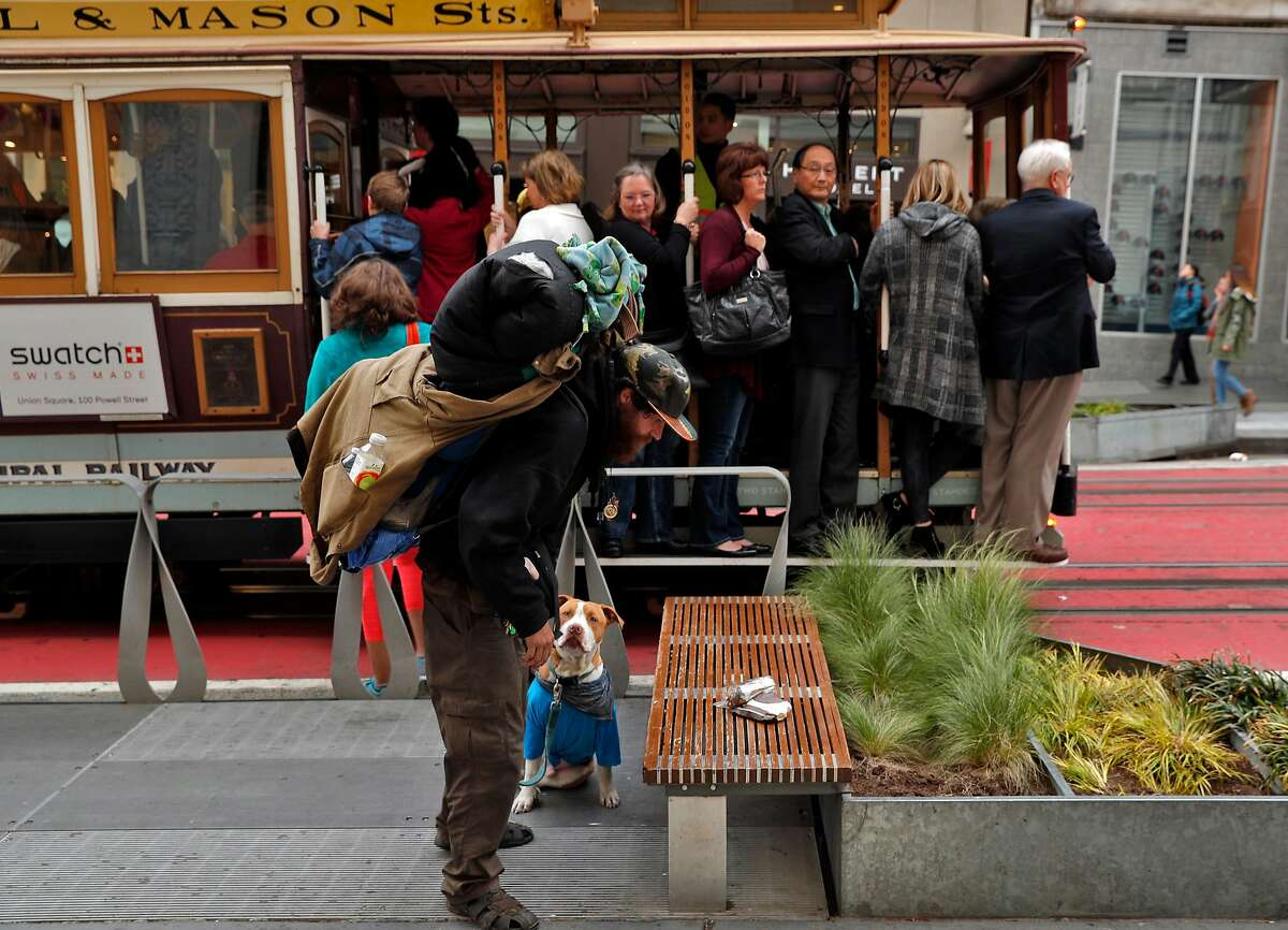 James Dowell, who is living on the streets with his dog, Kevin, picks up his belongings near a cable car at Powell Street, in San Francisco, Calif., on Wednesday, April 4, 2018. It's not just hotel owners who are getting the brunt of tourists' complaints about how disgusting San Francisco's streets have become. It's also S.F. Travel, the city's visitor bureau that's in charge of promoting the city and bringing conventions and conferences here. Increasingly, their clients are fed up and threatening to scratch SF off the convention circuit.
