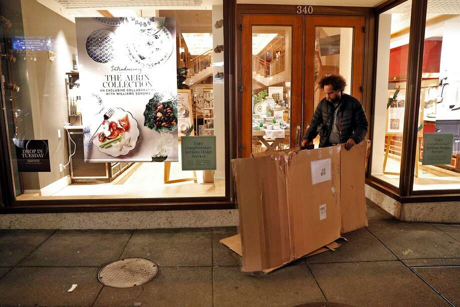 Chris Jones, who has lived on the streets for five years, sets up a cardboard barrier in the doorway of Williams-Sonoma near Union Square. Photo: Carlos Avila Gonzalez / The Chronicle