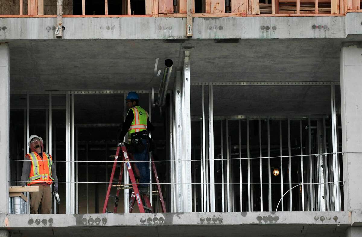 Laborers work on a construction site on Monday, April 16, 2018, in Oakland, Calif.