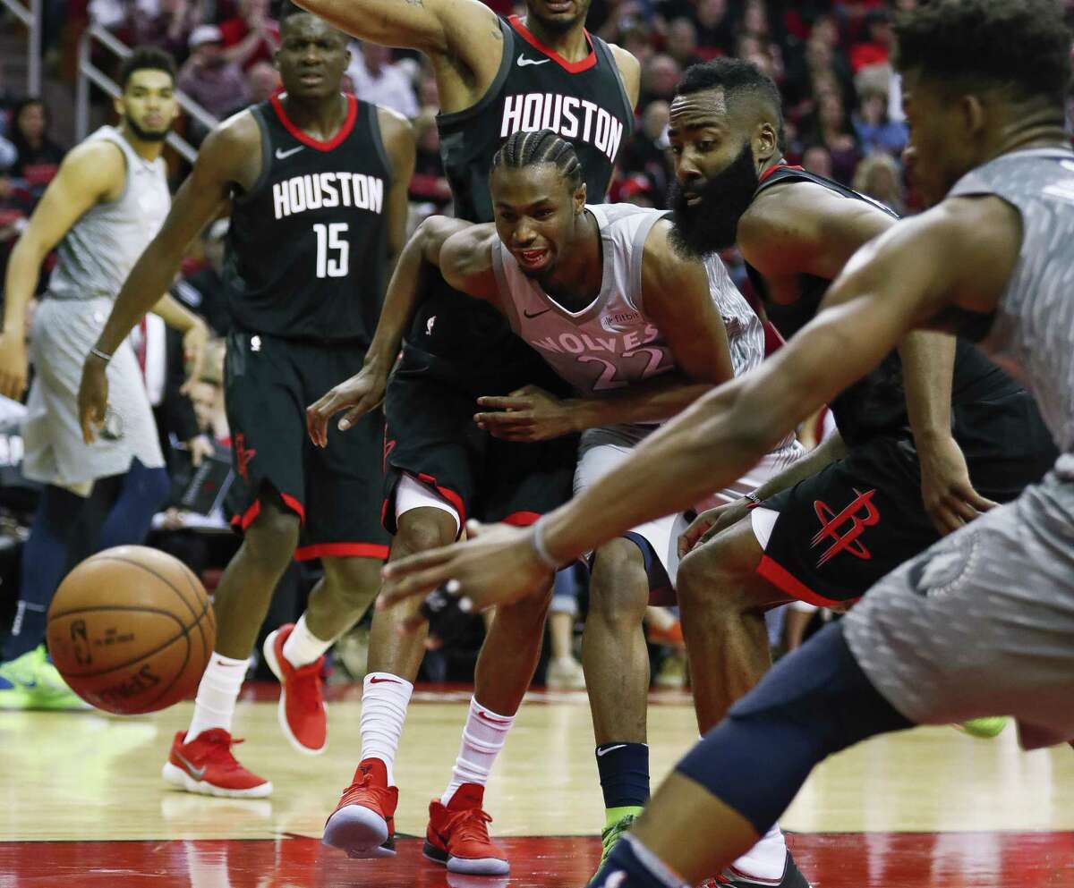 Houston Rockets guard James Harden (13) and Minnesota Timberwolves forward Andrew Wiggins (22) look after a loose ball during the fourth quarter of Game 1 of an NBA basketball first-round playoff series at Toyota Center on Sunday, April 15, 2018, in Houston. ( Brett Coomer / Houston Chronicle )