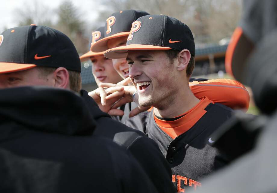 Princeton Tigers' Jake Boone huddles with his teammates before their game against the Monmouth Hawks in Princeton, N.J., Thursday, April 5, 2018. Boone is trying to put himself in position to make his the first four-generation major league family. His great-grandfather, Ray, was a two-time All-Star infielder from 1948-60. His grandfather, Bob, was a four-time All-Star catcher from 1972-90, then managed Kansas City from 1995-97 and Cincinnati from 2001-03. His father Bret, was a three-time All-Star second baseman in a big league career from 1992-05. And uncle Aaron is managing the New York Yankees. (AP Photo/Seth Wenig) Photo: Seth Wenig / Associated Press
