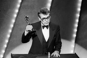 """(FILES) In this file photo taken on March 25, 1985 Czech-born US film director Milos Forman holds up his Oscar trophy for his film 'Amadeus' at the 57th Annual Academy Awards in Hollywood.  Oscar-winning Czech-born film director Milos Forman, known for """"One Flew Over the Cuckoo's Nest"""" and """"Amadeus,"""" has died aged 86, Czech media said on April 14, 2018. / AFP PHOTO / --/AFP/Getty Images"""