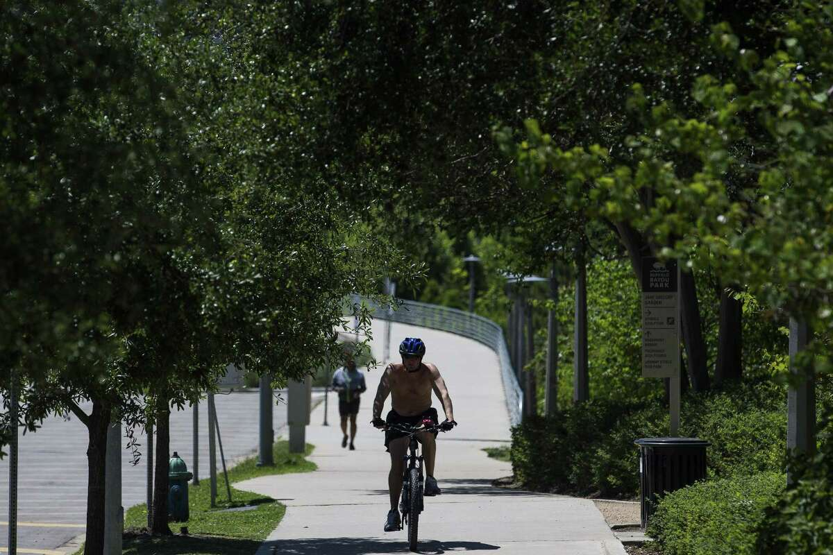 A cyclist rides through Buffalo Bayou Park next to Allen Parkway Monday, April 16, 2018 in Houston. A new partnership between city and county officials aims to improve bike and pedestrian access to downtown. (Michael Ciaglo / Houston Chronicle)