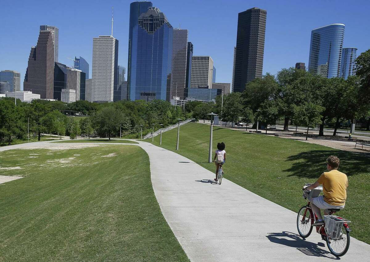 Cyclists ride through Buffalo Bayou Park next to Allen Parkway Monday, April 16, 2018 in Houston. A rare stretch of land that abuts the park will be developed, according to new documents filed with the city.