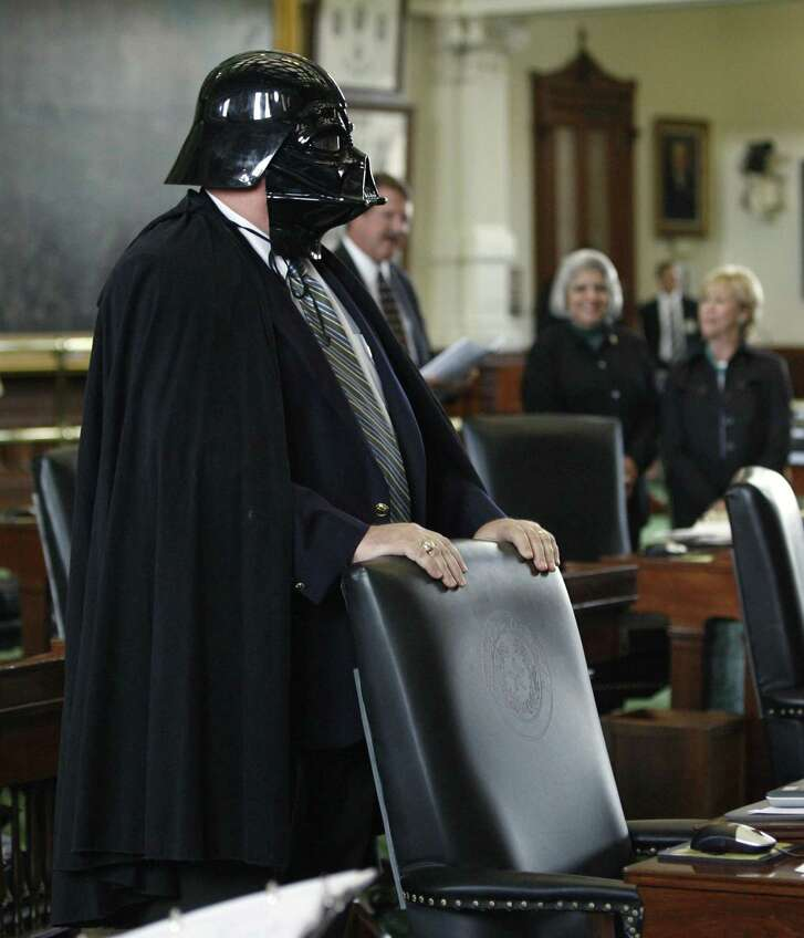 """Sen. Tommy Williams, R-The Woodlands, stands at his desk wearing a Darth Vader mask and cape during the session in the Texas Senate, Thursday, May 10, 2007, in Austin, Texas. In the background are, from left, Sen. Mike Jackson, R-La Porte, Sen. Judith Zaffirini, D-Laredo, and Sen. Florence Shapiro, R-Plano. The costume was a response to a newspaper editorial calling Williams the """"prince of darkness."""" (AP Photo/Harry Cabluck)"""
