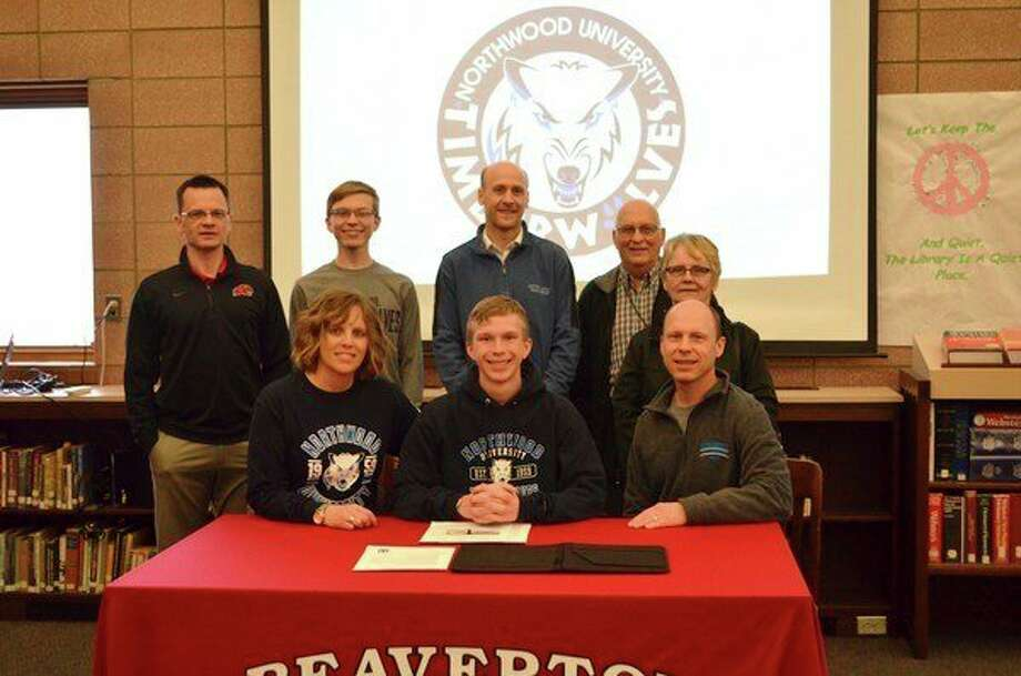 Beaverton's Parker Hayes (middle, front) is surrounded by family and coaches after signing a national letter of intent to run track and cross country at Northwood University, where he will also pursue a master's degree in NU's accelerated BBA/MBA program. (photo provided)