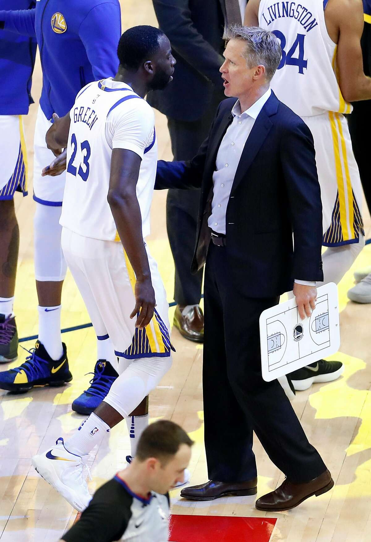 Golden State Warriors' head coach Steve Kerr and Draymond Green confer during a time out during 113-92 win over San Antonio Spurs in Game 1 of NBA Western Conference First Round playoff game at Oracle Arena in Oakland, Calif., on Saturday, April 14, 2018.