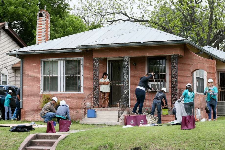 Highland Park resident Rosa Lopez (on porch), 56, watches volunteers begin to work on her home at 1123 E. Highland Blvd. during the city's second annual Rehabarama in the Highland Park neighborhood on Saturday, April 7, 2018.  Over three hundred volunteers gathered to help revive and revitalize twenty homes on the street with historic preservation in mind.  MARVIN PFEIFFER/mpfeiffer@express-news.net Photo: Marvin Pfeiffer, Staff / San Antonio Express-News / Express-News 2018