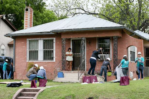 Highland Park resident Rosa Lopez (on porch), 56, watches volunteers begin to work on her home at 1123 E. Highland Blvd. during the city's second annual Rehabarama in the Highland Park neighborhood on Saturday, April 7, 2018.  Over three hundred volunteers gathered to help revive and revitalize twenty homes on the street with historic preservation in mind.  MARVIN PFEIFFER/mpfeiffer@express-news.net