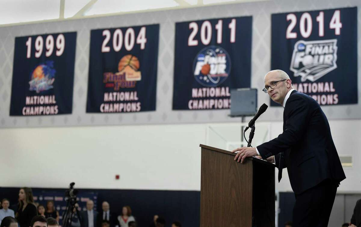 Dan Hurley speaks in front of UConn's championship banners after being introduced as the new men's basketball coach.