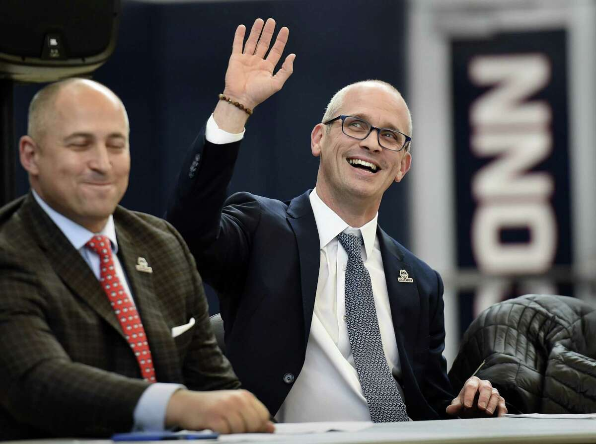 Dan Hurley waves as he is introduced as the new men's basketball coach at UConn. At left is UConn Athletic Director David Benedict.