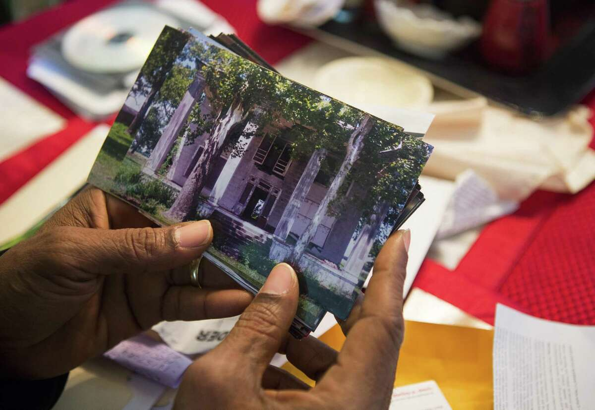 Reginald Moore, who has been striving for years to get recognition for the Old Imperial Farm cemetery that houses some bodies believed to be a part of the convict leasing system in Sugar Land, holds a picture of what was the Warden's house of the former Imperial Farm, Tuesday, April 10, 2018, in Sugar Land. ( Mark Mulligan / Houston Chronicle )