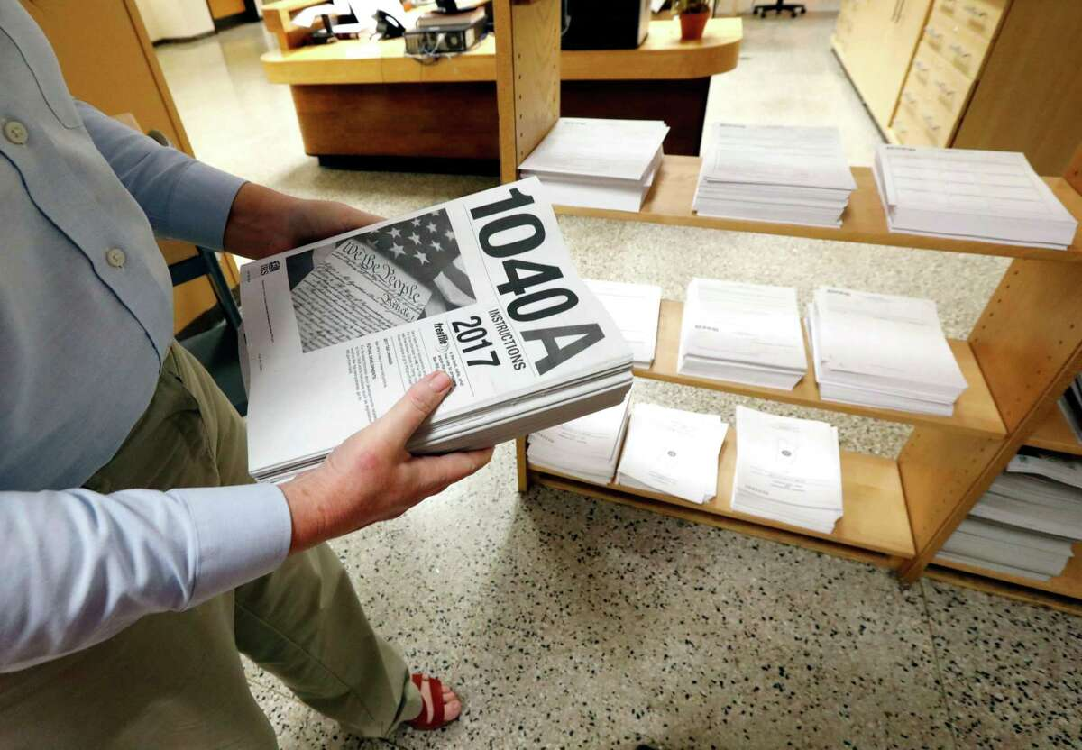 FILE- In this Feb. 15, 2018, photo, Susan Prendergast, reference supervisor at the Eudora Welty Library, in Jackson, Miss., adds additional federal tax filing information booklets on a shelf. Leading automated financial advisers ?- often called ?