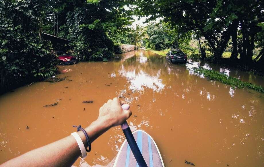 This Sunday, April 15, 2018, photo provided by Kauai resident James Hennessy shows the view as he maneuvers a stand-up paddleboarding along his flooded street in Haena, Hawaii. Heavy rains on Kauai let up on Monday, which helped emergency workers better rescue people stranded by flooding on the Hawaiian island. Photo: James Hennessy/AP