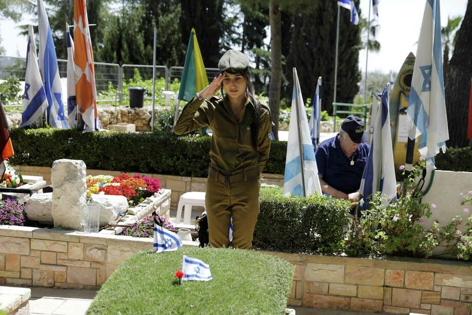 A female Israeli soldier salutes after placing the national flag on the grave of a fallen soldier at the Mount Herzl military cemetery in Jerusalem on April 16, 2018, two days before the annual memorial day, honoring troops killed in service of their country. Israel will mark the Remembrance Day from April 17 after sunset till April 18 to commemorate over 23,646 fallen soldiers since 1860, just before the celebrations of the 70th anniversary of its creation according to the Jewish calendar. Photo: MENAHEM KAHANA, Contributor / AFP/Getty Images / AFP or licensors