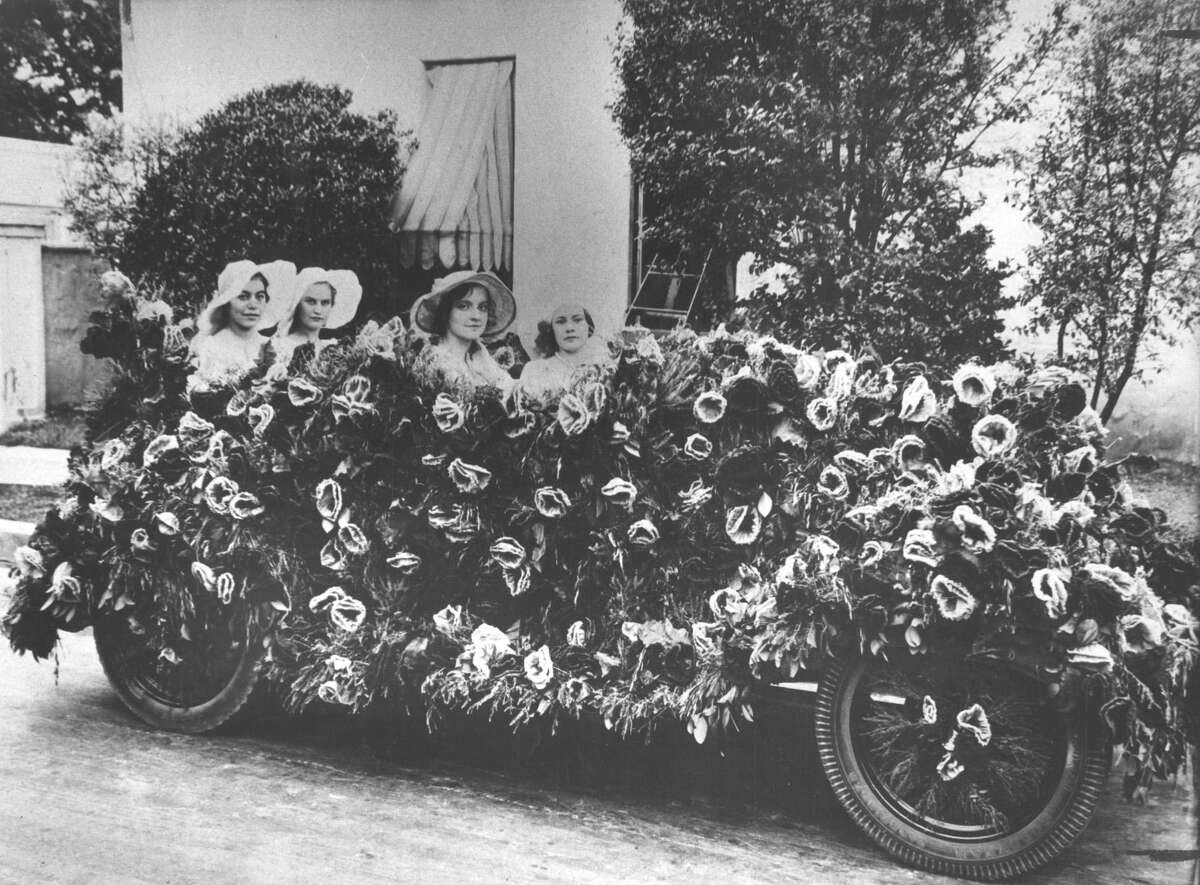 In early Battle of Flowers parades automobiles, such as this one, were covered in flowers. The parade started with carriages covered in flowers and participants pelting one another with flowers in a procession at Alamo Plaza
