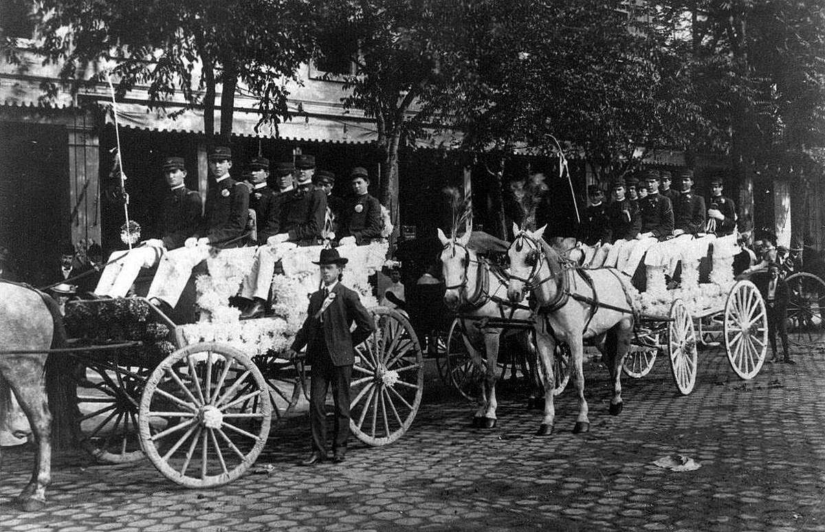 Peacock Military Academy's carriage in the 1904 Battle of Flowers Parade stands in Alamo Plaza on mesquite wood block pavers.