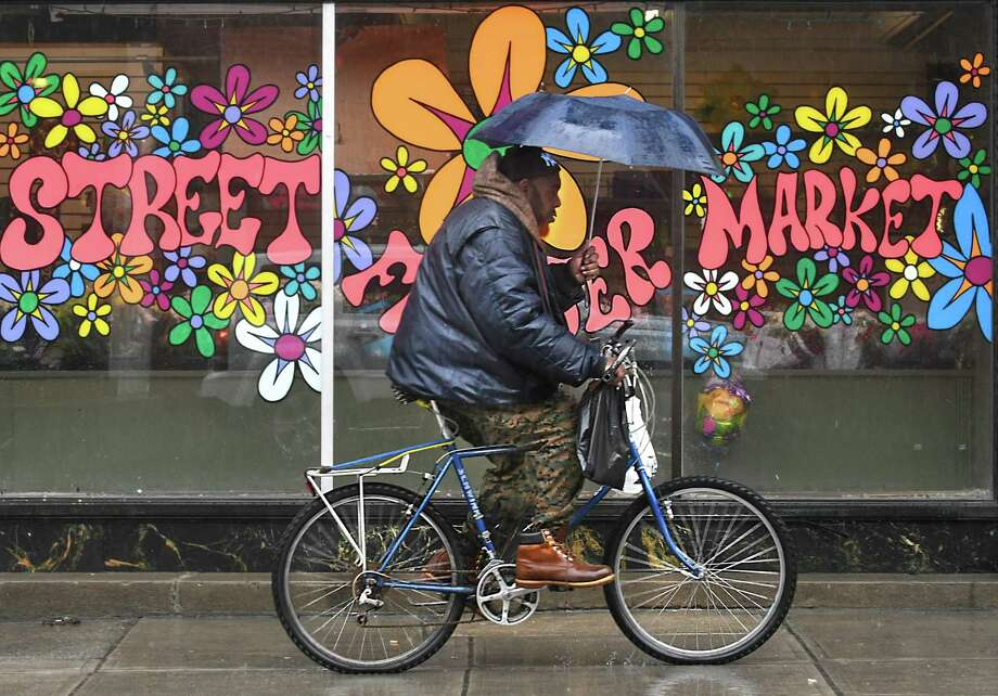 A bicyclist makes his way down Lark St. holding an umbrella during a rain storm on Monday, April 16, 2018 in Albany, N.Y. (Lori Van Buren/Times Union) Photo: Lori Van Buren
