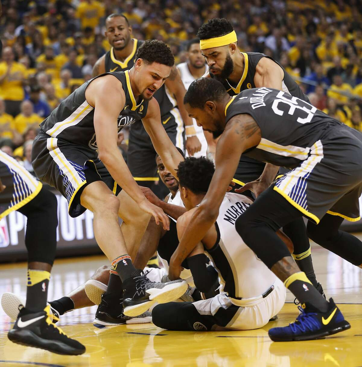 Golden State Warriors' Klay Thompson, JaVale McGee and Kevin Durant surround San Antonio Spurs' Dejounte Murray in the first quarter during game 2 of round 1 of the Western Conference Finals at Oracle Arena on Monday, April 16, 2018 in Oakland, Calif.