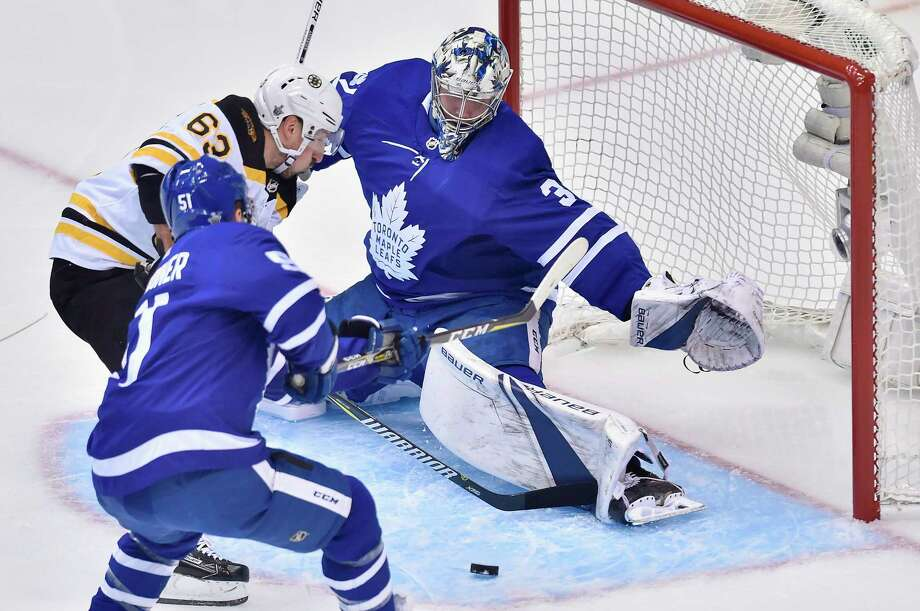 Boston Bruins left wing Brad Marchand (63) looks for a rebound as Toronto Maple Leafs goaltender Frederik Andersen (31) makes a save and Toronto Maple Leafs defenseman Jake Gardiner (51) defends during first period NHL round one playoff hockey action in Toronto on Monday, April 16, 2018. (Nathan Denette/The Canadian Press via AP) Photo: Nathan Denette / The Canadian Press