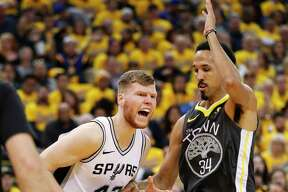 San Antonio Spurs' Davis Bertans gets past Golden State Warriors' Shaun Livingston in the second quarter during game 2 of round 1 of the Western Conference Finals at Oracle Arena on Monday, April 16, 2018 in Oakland, Calif.