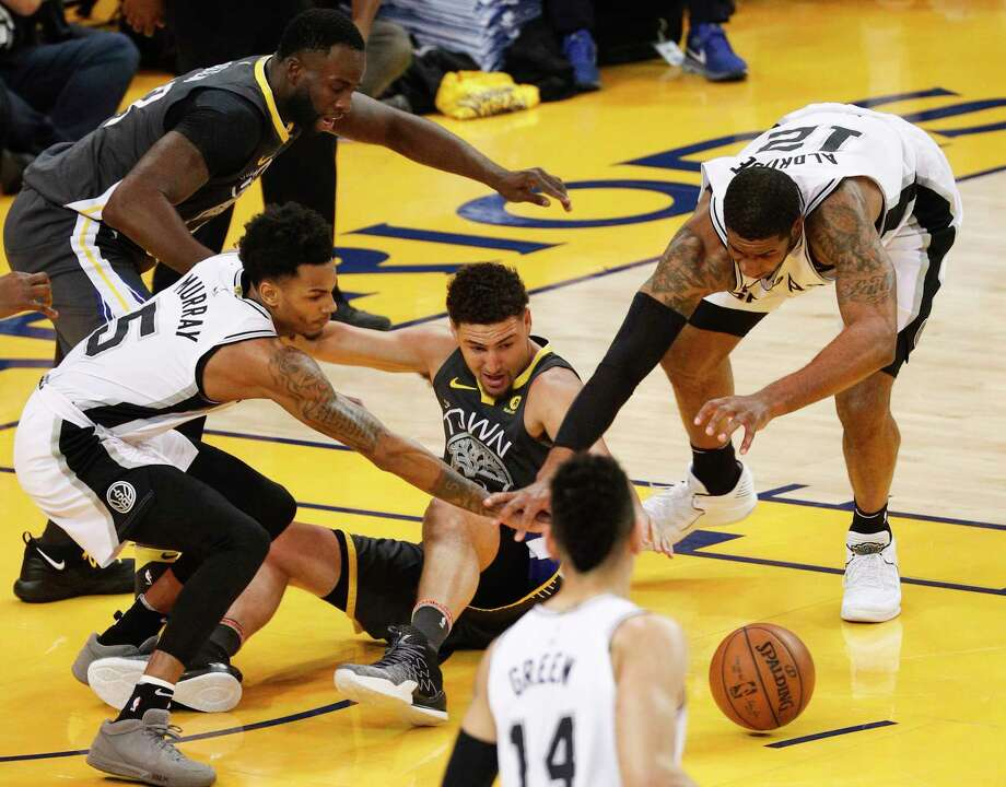 San Antonio Spurs' Dejounte Murray and LaMarcus Aldridge fight Golden State Warriors' Klay Thompson for a loose ball in the first quarter during game 2 of round 1 of the Western Conference Finals at Oracle Arena on Monday, April 16, 2018 in Oakland, Calif. Photo: Michael Macor, The Chronicle / online_yes