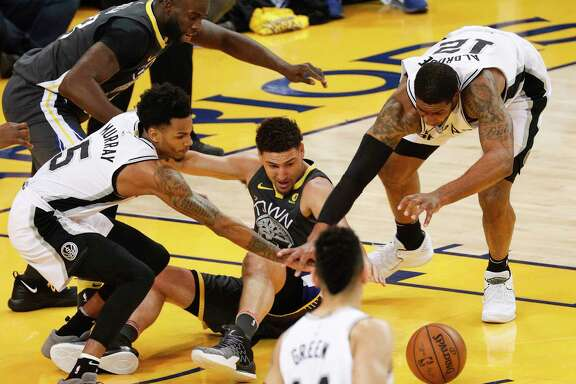 San Antonio Spurs' Dejounte Murray and LaMarcus Aldridge fight Golden State Warriors' Klay Thompson for a loose ball in the first quarter during game 2 of round 1 of the Western Conference Finals at Oracle Arena on Monday, April 16, 2018 in Oakland, Calif.