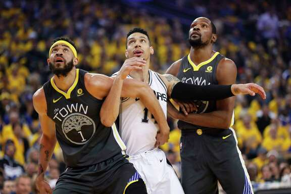 Golden State Warriors' JaVale McGee and Kevin Durant fight for position against San Antonio Spurs' Danny Green in the first quarter during game 2 of round 1 of the Western Conference Finals at Oracle Arena on Monday, April 16, 2018 in Oakland, Calif.