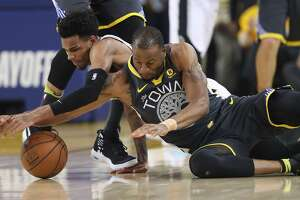 Golden State Warriors' Andre Iguodala fights San Antonio Spurs' Dejounte Murray for a loose ball in the first quarter during game 2 of round 1 of the Western Conference Finals at Oracle Arena on Monday, April 16, 2018 in Oakland, Calif.