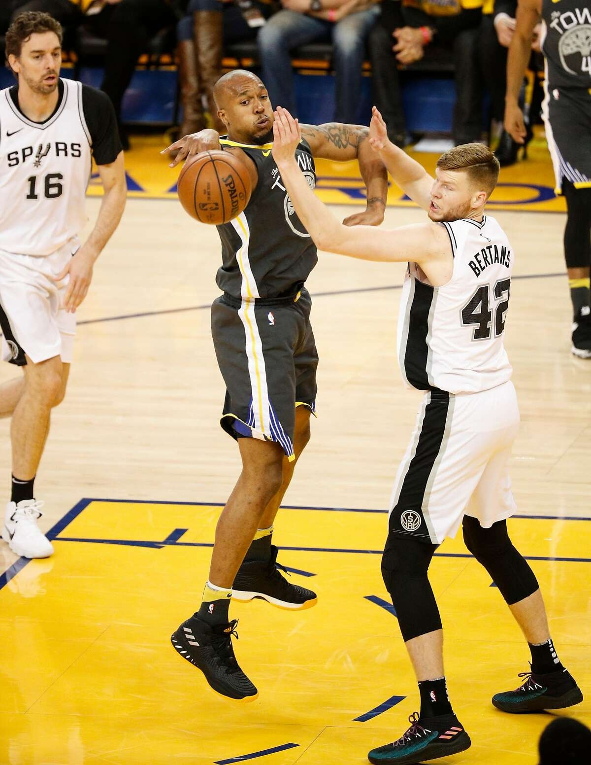 Golden State Warriors' David West passes off against San Antonio Spurs' Davis Bertans in the second quarter during game 2 of round 1 of the Western Conference Finals at Oracle Arena on Monday, April 16, 2018 in Oakland, Calif.