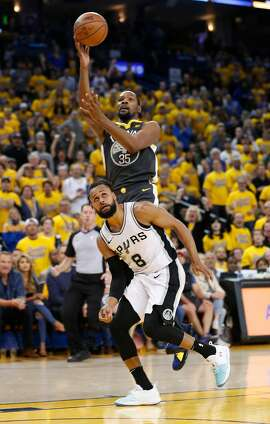 Golden State Warriors' Kevin Durant shoots over San Antonio Spurs' Patty Mills in the third quarter during game 2 of round 1 of the Western Conference Finals at Oracle Arena on Monday, April 16, 2018 in Oakland, Calif.