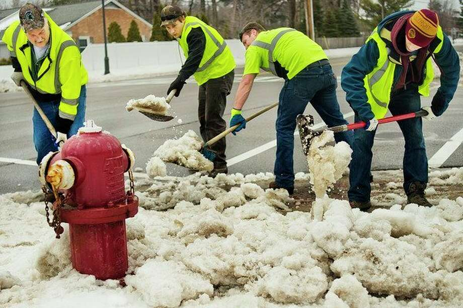 From left, City of Midland employees Brad Bell, 54, Brandon Rytlewski, 20, Justin Hunt, 26 and Luke Schmidt, 21, shovel snow off of a crosswalk at the intersection of Dilloway and Eastman on Monday afternoon. (Katy Kildee/kkildee@mdn.net)