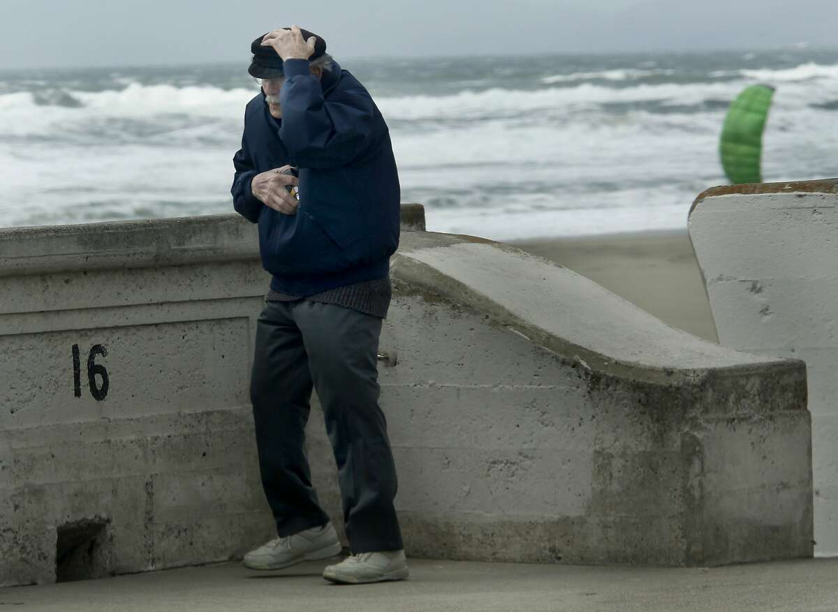 A passing weather front made San Francisco, Calif. a very windy day Wednesday April 21, 2010. Longtime San Francisco resident Emile Pavlou ventured down to Ocean Beach to get a picture of the waves but had to hold onto his hat with the strong gusts.