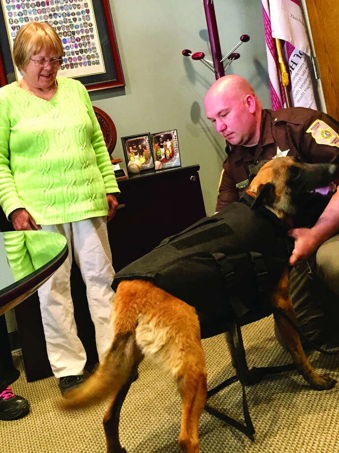 Madison County Sheriff's Department K-9 Havoc models his bullett-proof vest for handler Deputy Kyle Doolen, right, and Barb Fry of the Mixed Breed Dog Club, which donated the item Photo: Steve Horrell