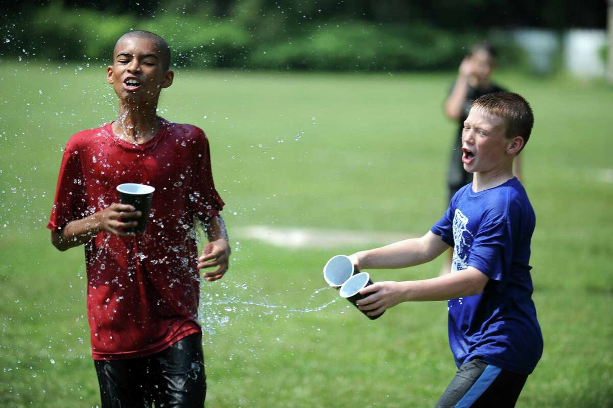 Quentin Pitter, left, and Jack Balocca cool off with water play during a graduation party for Peck Place School's sixth grade class Wednesday, June 20, 2012 at the Orange Country Fair grounds in Orange, Conn. Mom Tina Saxa hosted the party for the graduating class and hosted two previous parties when her younger children graduated from Peck Place Elementary School.