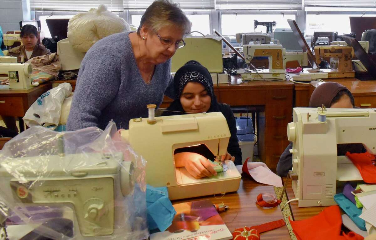 Mary Dwileski watches Fatima, a refugee from Afghanistan, as she practices her sewing skills on a square handkerchief at a class in Rensselaer's McManus Center on April 14, 2018. The class, sponsored by the Literacy Volunteers of Rensselaer County, takes place every Saturday to help refugees practice their sewing and English skills. (Massarah Mikati/Times Union)