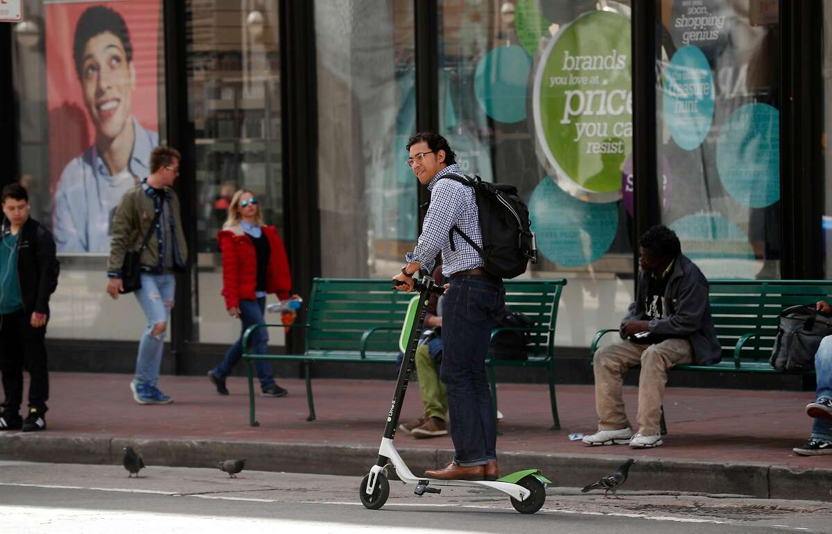 Cruising down Mission st. on a Lime scooter as seen on Mon. April 9, 2018, in San Francisco, Calif.