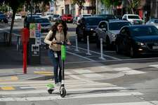 A rider aboard a Lime scooter cruises down Folsom St. as seen on Mon. April 9, 2018, in San Francisco, Calif.