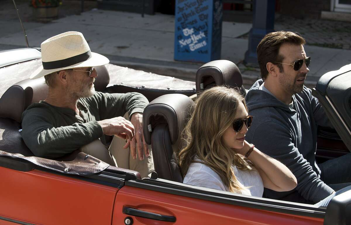 This image released by Netflix shows Ed Harris, from left, Elizabeth Olsen and Jason Sudeikis in a scene from
