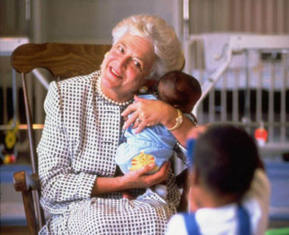 First Lady Barbara Bush holding a baby while two-year-old child takes photo with a toy camera at a hospice for children with AIDS.