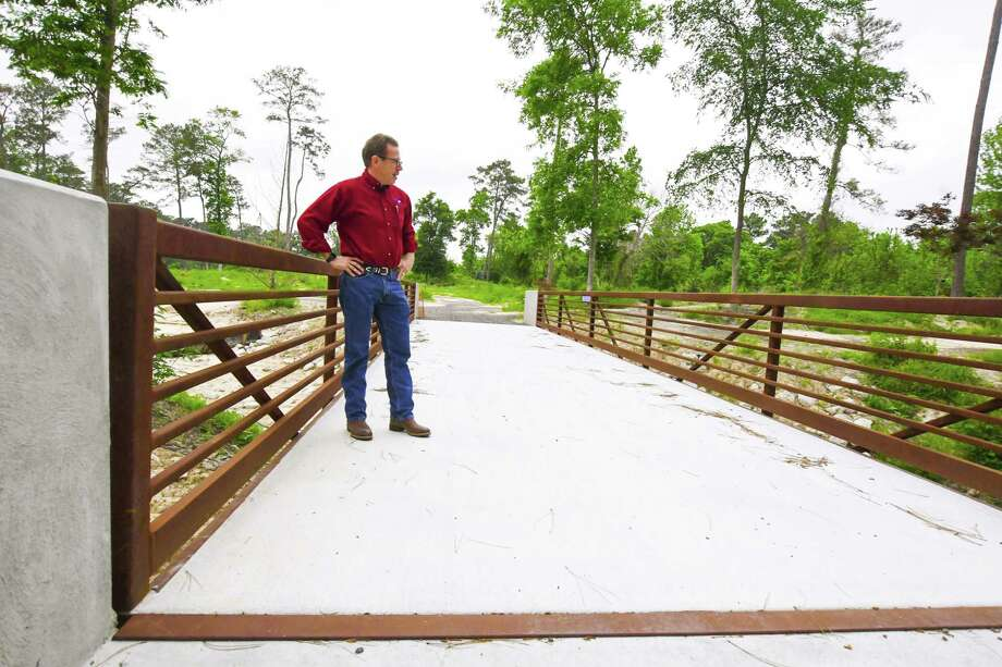 Jim Nutter, interim director of Mercer Arboretum and Botanic Gardens, views the new metal bridge that is replacing a wooden bridge east of the gardens near Cypress Creek that had been previously damaged in the Tax Day floods of 2016. Photo: Tony Gaines /HCN, Photographer