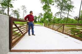 Jim Nutter, interim director of Mercer Arboretum and Botanic Gardens, views the new metal bridge that is replacing a wooden bridge east of the gardens near Cypress Creek that had been previously damaged in the Tax Day floods of 2016.