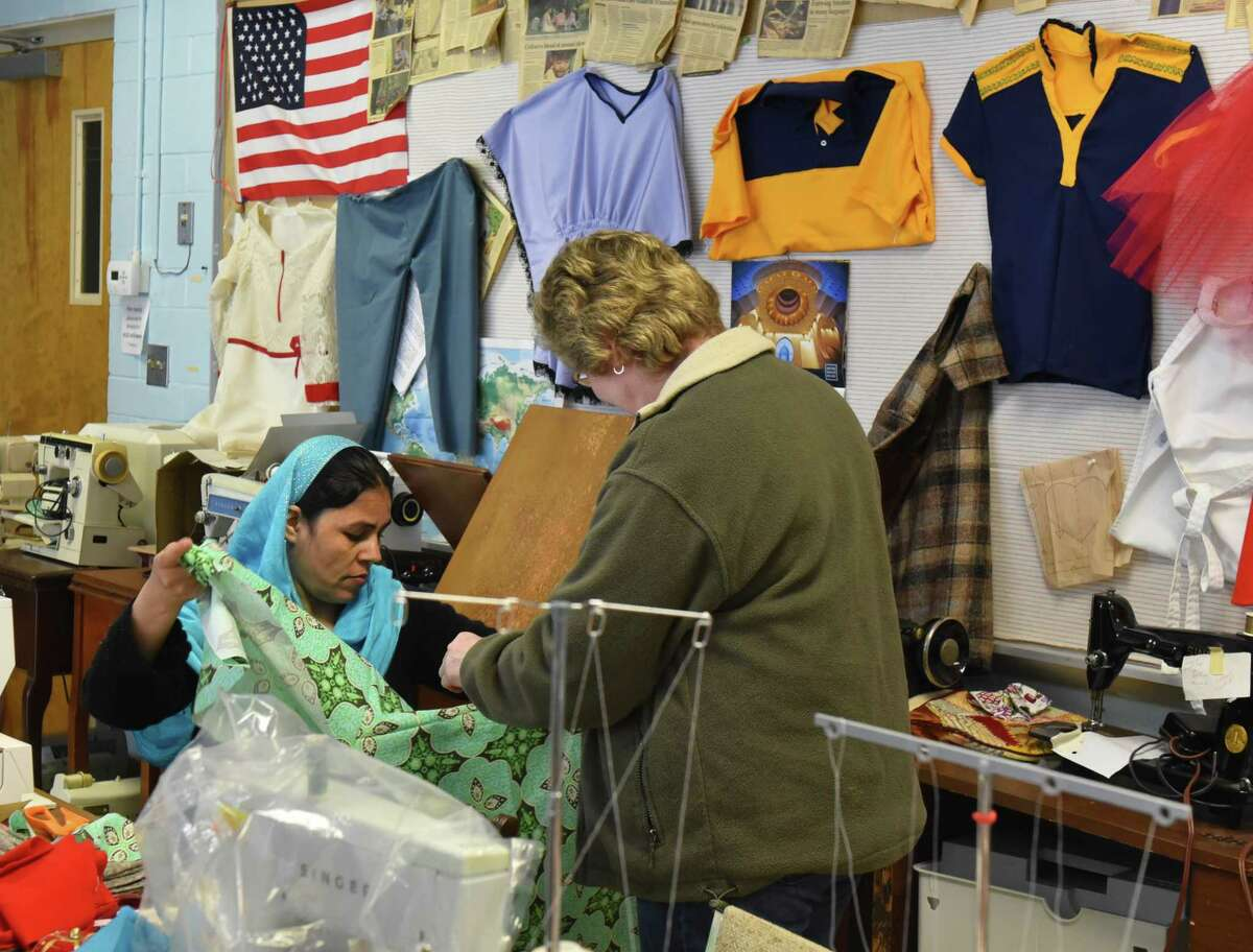 Fatima, a refugee from Afghanistan, shows a traditional dress she's sewing to Judith Smith, executive director of the Literacy Volunteers of Rensselaer County, at a sewing class in Rensselaer's McManus Center on April 14, 2018. The class, sponsored by the Literacy Volunteers of Rensselaer County, takes place every Saturday to help refugees practice their sewing and English skills. (Massarah Mikati/Times Union)