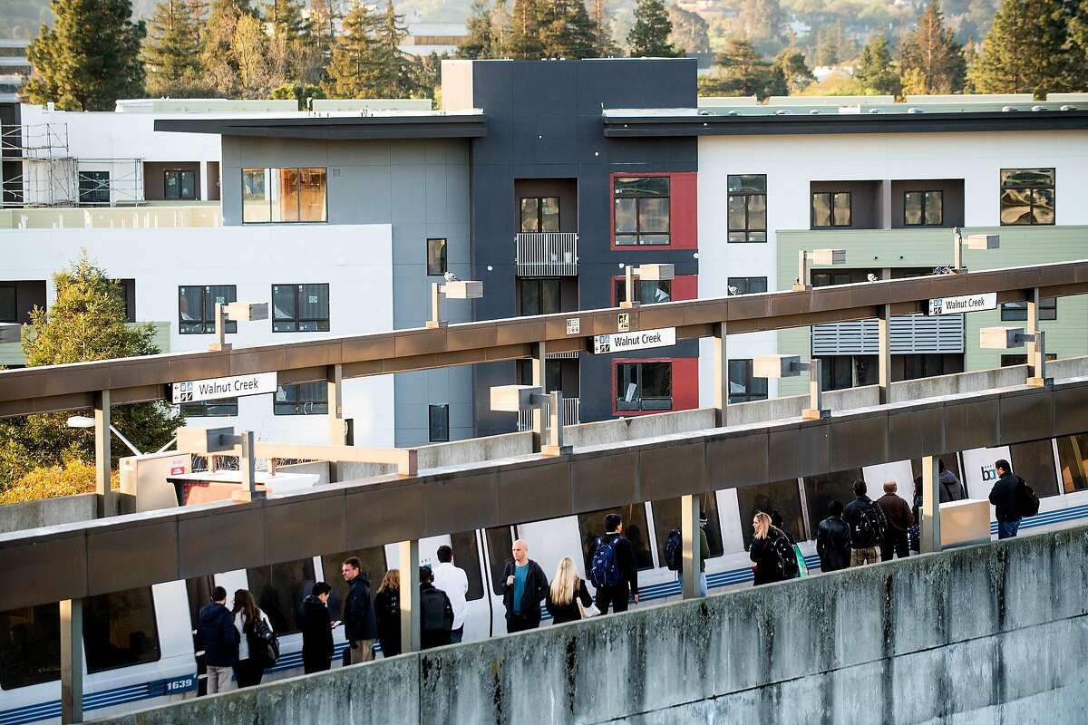 Commuters line a platform at the Walnut Creek BART station on Friday, March 23, 2018, in Walnut Creek, Calif. In the background is the Vaya housing complex, a 178 unit transit-oriented development slated to open this year.