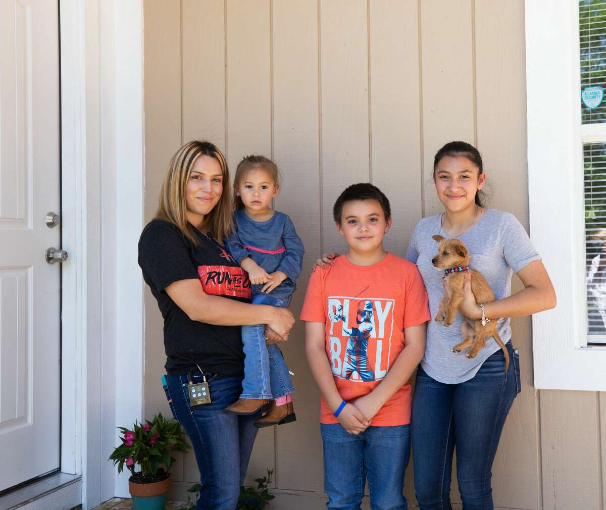 Margarita Garza and her three children, Jose Luis, Sophia and Noemi Tudon, pose outside their homein the Greenbrooks subdivision near Atascocita. The home was badly damaged by Hurricane Harvey flooding. Even though they had help getting the home livable again, Garza couldn't afford new furniture. The Houston Rockets, Rooms To Go and Marie Flanigan Interiors brought everything together for them.