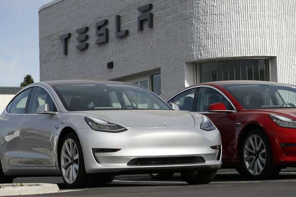 In this Sunday, April 15, 2018, photograph, unsold 2018 Model 3 Long Range vehicles sit on a Tesla dealer's lot in the south Denver suburb of Littleton, Colo. (AP Photo/David Zalubowski)